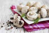 stock photo of champignons  - champignon mushrooms on a old wooden background - JPG