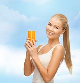 health, diet and food concept - young woman holding glass of orange juice