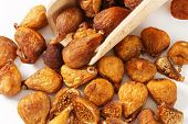 dried figs with wooden measuring spoon