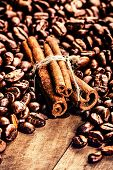 Roasted Coffee Beans And Cinnamon Sticks On Grunge Wooden Background Macro