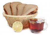 Wicker basket with black bread and tea on a white background