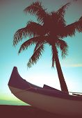 stock photo of waikiki  - Retro Styled Photo Of Outrigger Canoe And Palm Tree In Hawaii - JPG