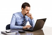 Young business person at office desk looking on laptop