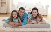 stock photo of family love  - Happy family on floor lying in living - JPG