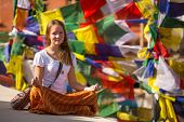 Girl sitting in the Lotus position on Buddhist stupa, prayer flags flying in the background.