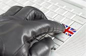 Hacking Uk Concept With Hand Wearing Black Leather Glove Pressing Enter Key With Flag Overlaid
