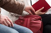 stock photo of shoplifting  - Man trying to steal something lady sitting in waiting room - JPG