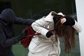 stock photo of yanks  - A masked thief attacking an innocent woman in the street - JPG