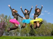 stock photo of showgirl  - three cheerful showgirls jumping outdoors in sunny day - JPG