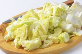 chopped chinese cabbage and kitchen knife on oval wooden cutting board