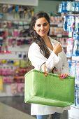 Female pharmacist in drugstore stocking shelves
