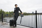 Full length of businessman with luggage leaning on railing along river