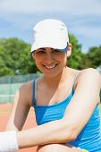 Pretty tennis player smiling at camera on a sunny day