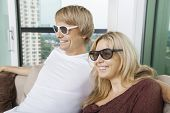 Happy couple wearing 3D glasses while sitting on sofa at home