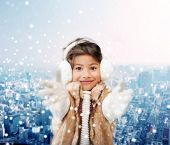 winter, christmas, childhood, happiness and people concept - smiling little girl in winter clothes