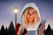 Sexy santa girl opening gift against lamppost at night