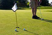 Golfer Practicing Putting Golf Balls