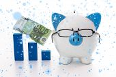 Snow falling against piggy bank wearing glasses with blue graph model and hundred euro note