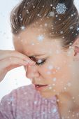 Young woman suffering from headache against snow falling