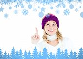Young woman wearing a colorful hat pointing upwards with her finger against snow flake frame in blue