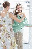 Young women shopping in clothes store against snow falling