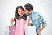 Attractive young couple with shopping bags against snow falling