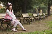 stock photo of lolita  - Japanese girl in lolita cosplay fashion sitting on a bench - JPG