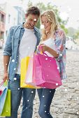 Hip young couple looking at their shopping bags against snow falling