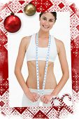 Slim woman with a measure tape against christmas themed page