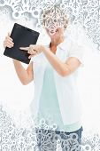 Happy mature woman pointing to tablet pc against snowflakes on silver