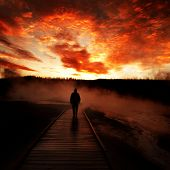 Sunrise near Yellowstone geysers with steam and silhouette of person on boardwalk