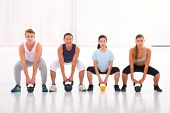 Multiethnic Group Of People Doing Kettlebell Crossfit Exercise