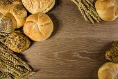 foto of bread rolls  - Different kind of freshly baked bread and rolls on wooden table - JPG
