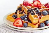 pic of dessert plate  - Waffles with berries and honey on wooden table