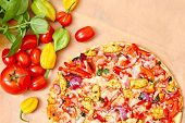 Pizza with vegetables on wooden table