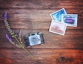 Vintage photo camera on a wooden table with some snapshots and a flower