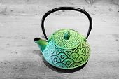 Green Teapot On Grey Wooden Background