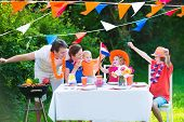 pic of holland flag  - Happy big Dutch family with kids celebrating a national holiday or sport victory having fun at a grill party in a garden decorated with flags of Netherlands screaming Hup Holland - JPG