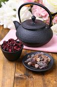 Black teapot, bowl and hibiscus tea on color wooden table, on bright background