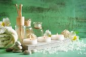Composition of spa treatment, candles in bowl with water on wooden background