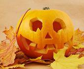Pumpkin Jack-o'-lantern over maple-leaf