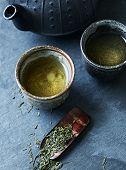 A cast iron tea pot and green tea in ceramic cups