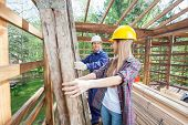 Smiling male construction worker working with female colleague in wooden cabin at site