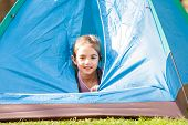 Portrait of cute girl inside tent at park