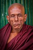 YANGON, MYANMAR - JANUARY 3, 2014: Portrait of ascetic Buddhist monk meditating in Shwedagon Paya pagoda