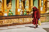 YANGON, MYANMAR - JANUARY 3, 2014: Old Buddhist monk walking in Shwedagon Paya pagoda - the most sacred Buddhist pagoda in Myanmar