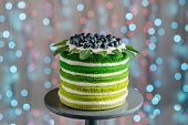 stock photo of cake stand  - Nice sponge happy birthday cake with mascarpone and grapes on the cake stand on festive light bokeh - JPG