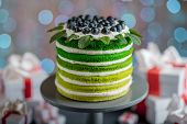 foto of sponge-cake  - Nice sponge happy birthday cake with mascarpone and grapes with on the cake stand with gift boxes on festive light bokeh background - JPG