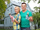 repair, people, real estate, home and family concept - smiling couple with paint brushes over house background