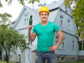 repair, construction, people, building and maintenance concept - smiling male manual worker in protective helmet holding electric drill over house background